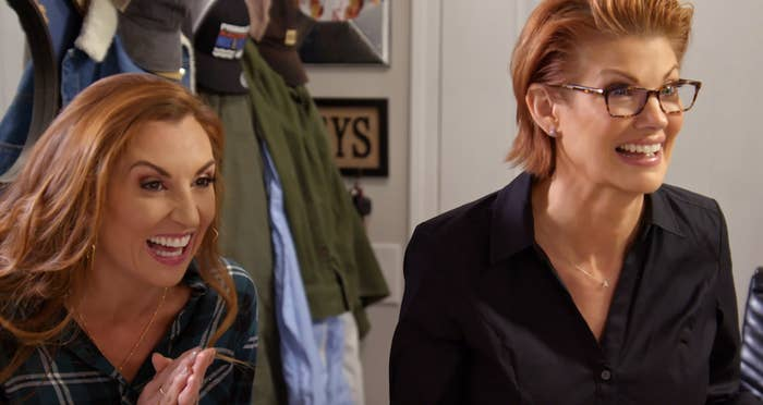 Two redheaded women grin at something off-camera