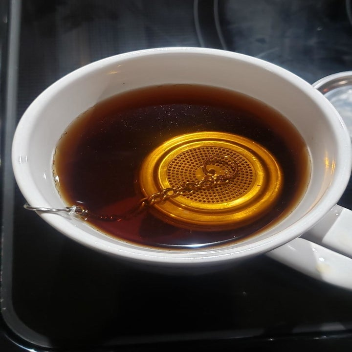 A reviewer photo of the strainer in a mug filled with black tea