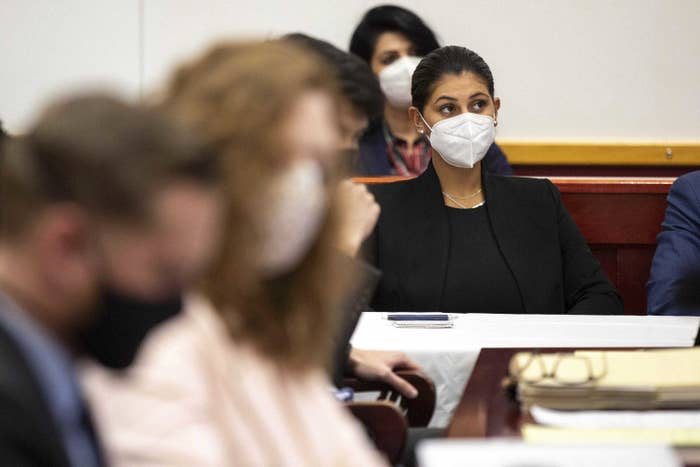 A woman wearing a face mask sits in court