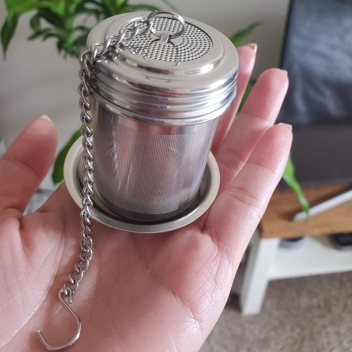 A reviewer photo of a hand holding out the mesh tea strainer on the included saucer