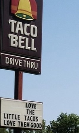 sign reading love the little tacos love them good below a Taco Bell sign