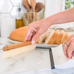 A pair of hands sweeping crumbs on the counter into the dustpan