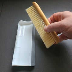 A hand holding a small brush with a white dustpan sitting nearby
