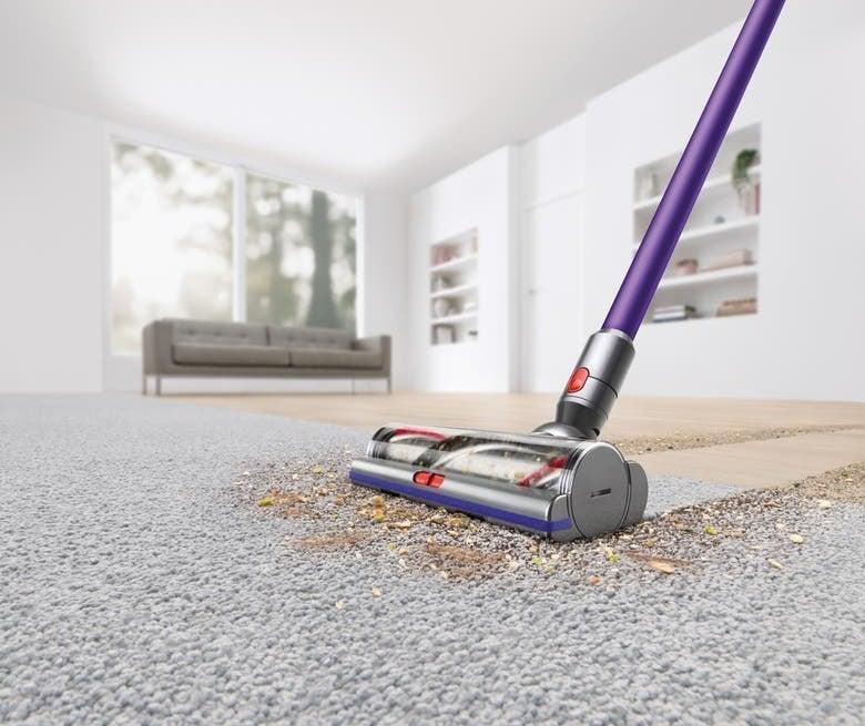 The purple vacuum shown sucking up a trail of debris