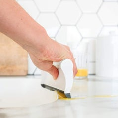 A hand using the squeegee end of the dust pant to slide spilled liquid on the counter into the sink