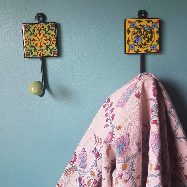 Two of the three ceramic wall hangers with a patterned blanket hanging off of one