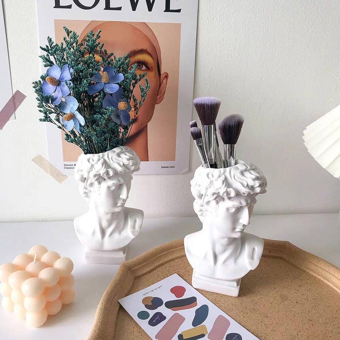 Two bus vases with flowers and makeup brushes inside
