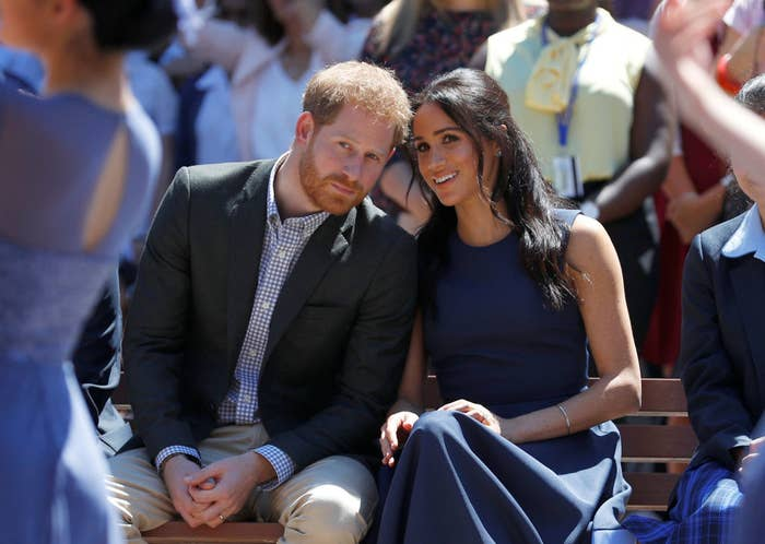 Harry and Meghan sitting together on a bench; Harry is leaning towards Meghan while she smiles