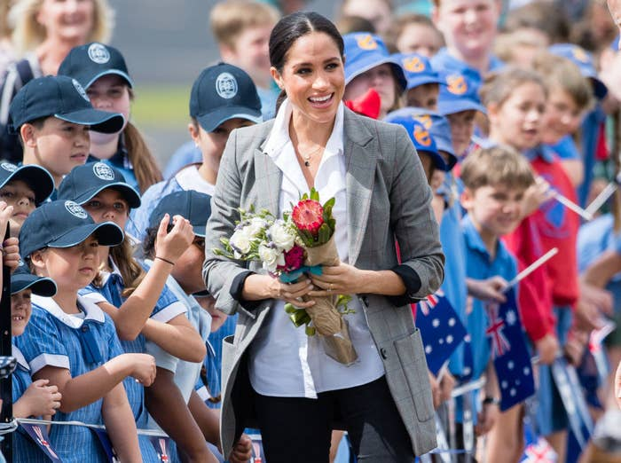 Meghan greeting school children at Dubbo Airport; she is holding bouquets of flowers