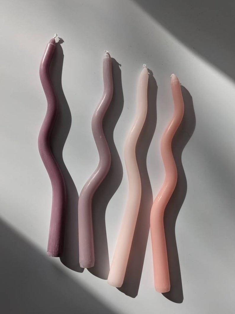 four squiggly candles in a gradient of the same shade