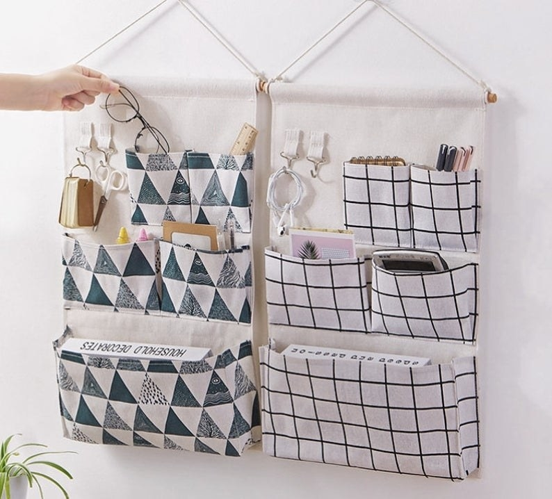 Two patterned wall pocket organizers with five pockets and two hooks holding books, electronics, and stationery inside