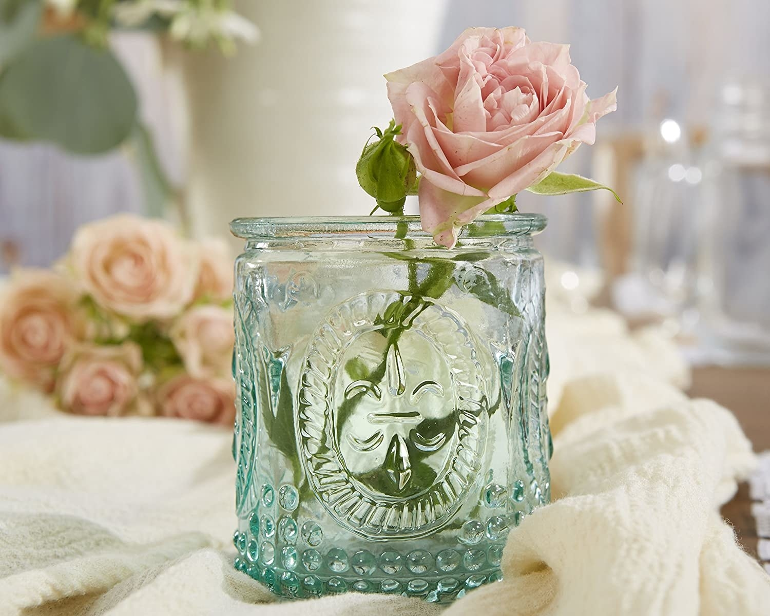 The small glass jar with a rose inside of it