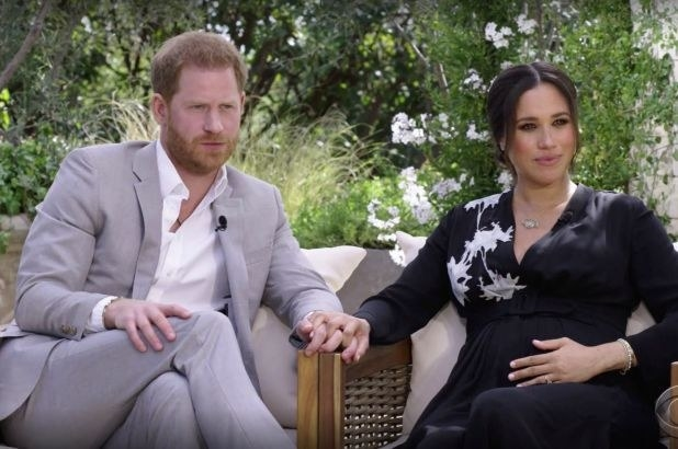 Harry and Meghan sitting on two chairs while holding hands