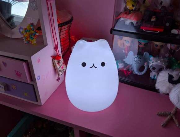 white glowing kitty night light sitting on a desk