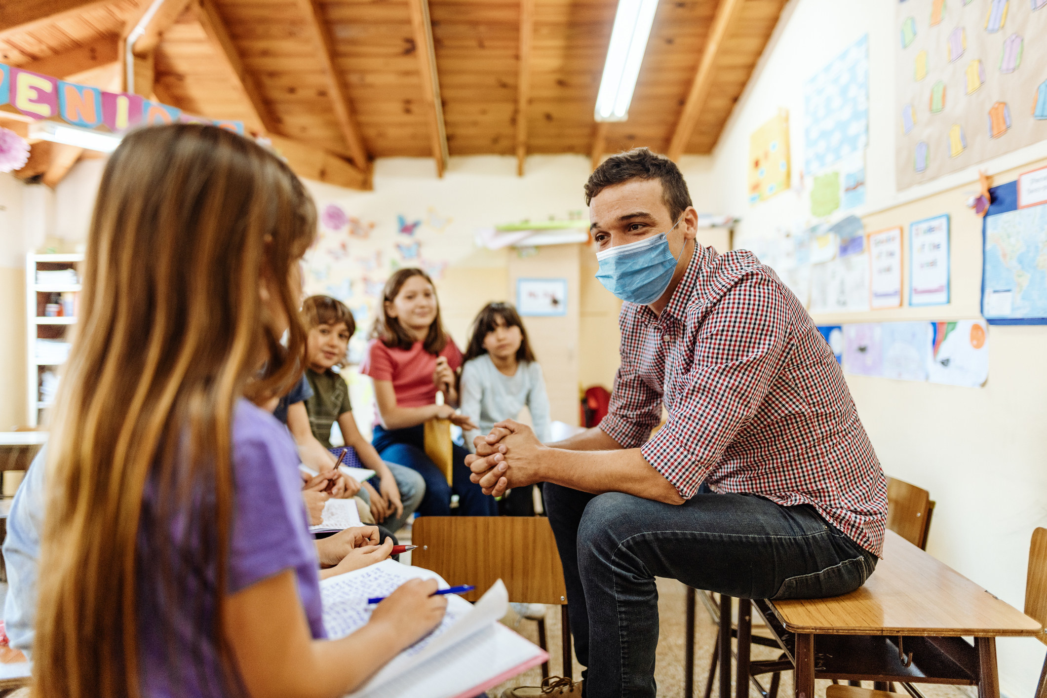 A teacher sitting on top of a desk, wearing a mask, and talking to his students