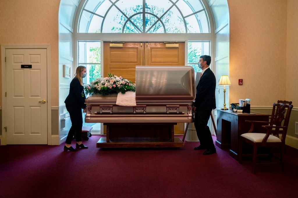 Two people carrying a casket in a funeral home while wearing masks