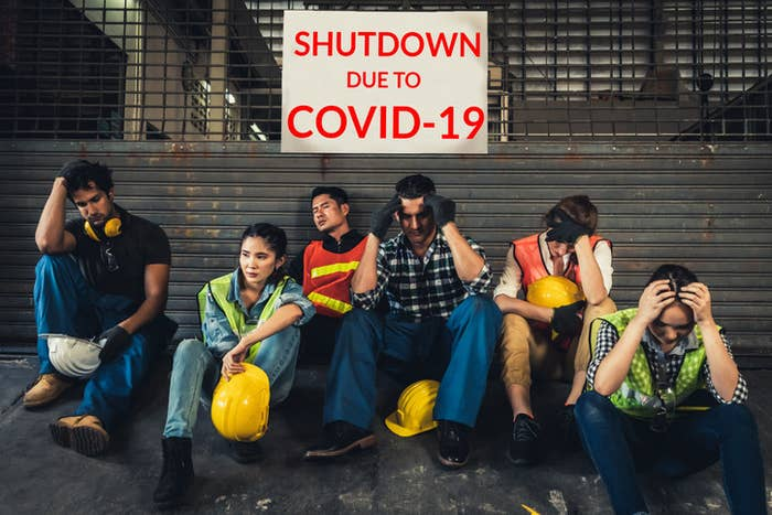 Construction workers sitting down on a site, unemployed because of COVID-19