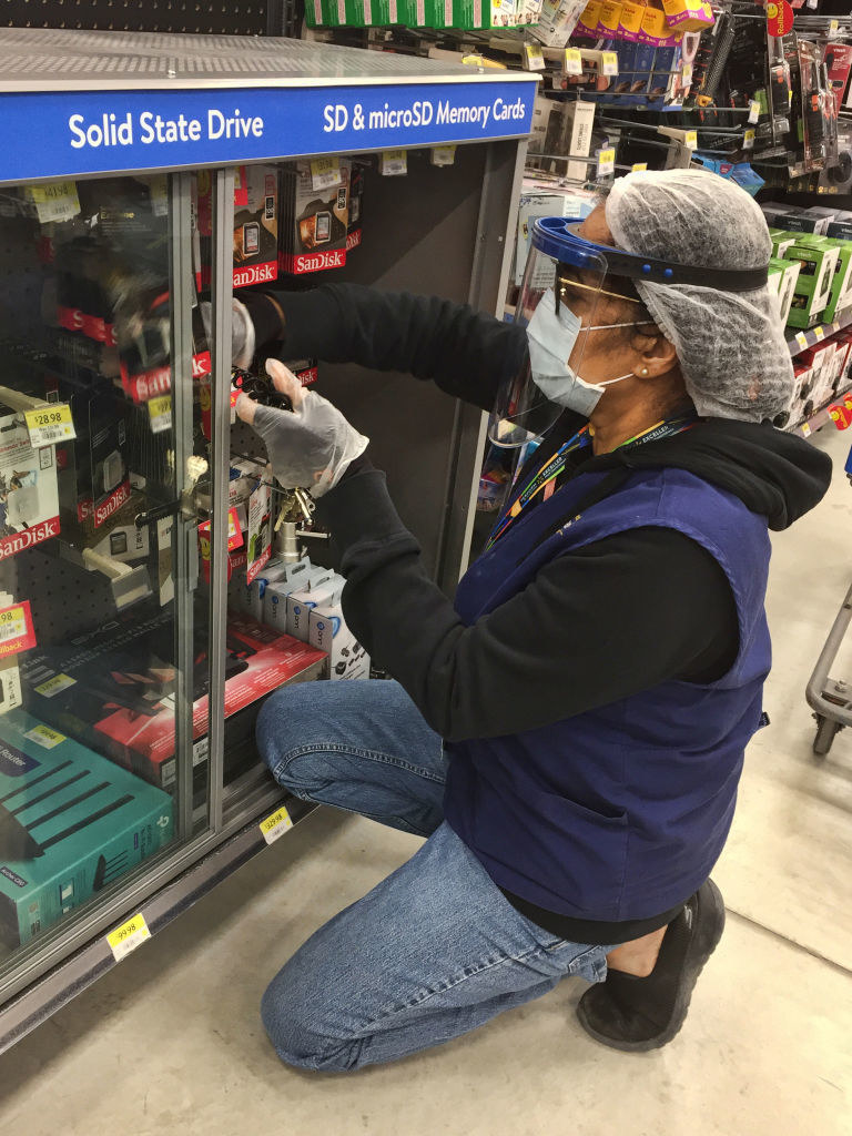 A Walmart employee wearing a face mask and face shield while stocking items in a cabinet