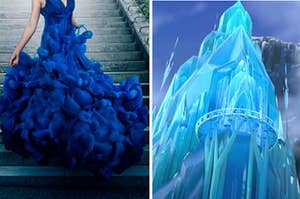A woman is wearing a blue gown as she walks down the steps with a tall ice castle on the right