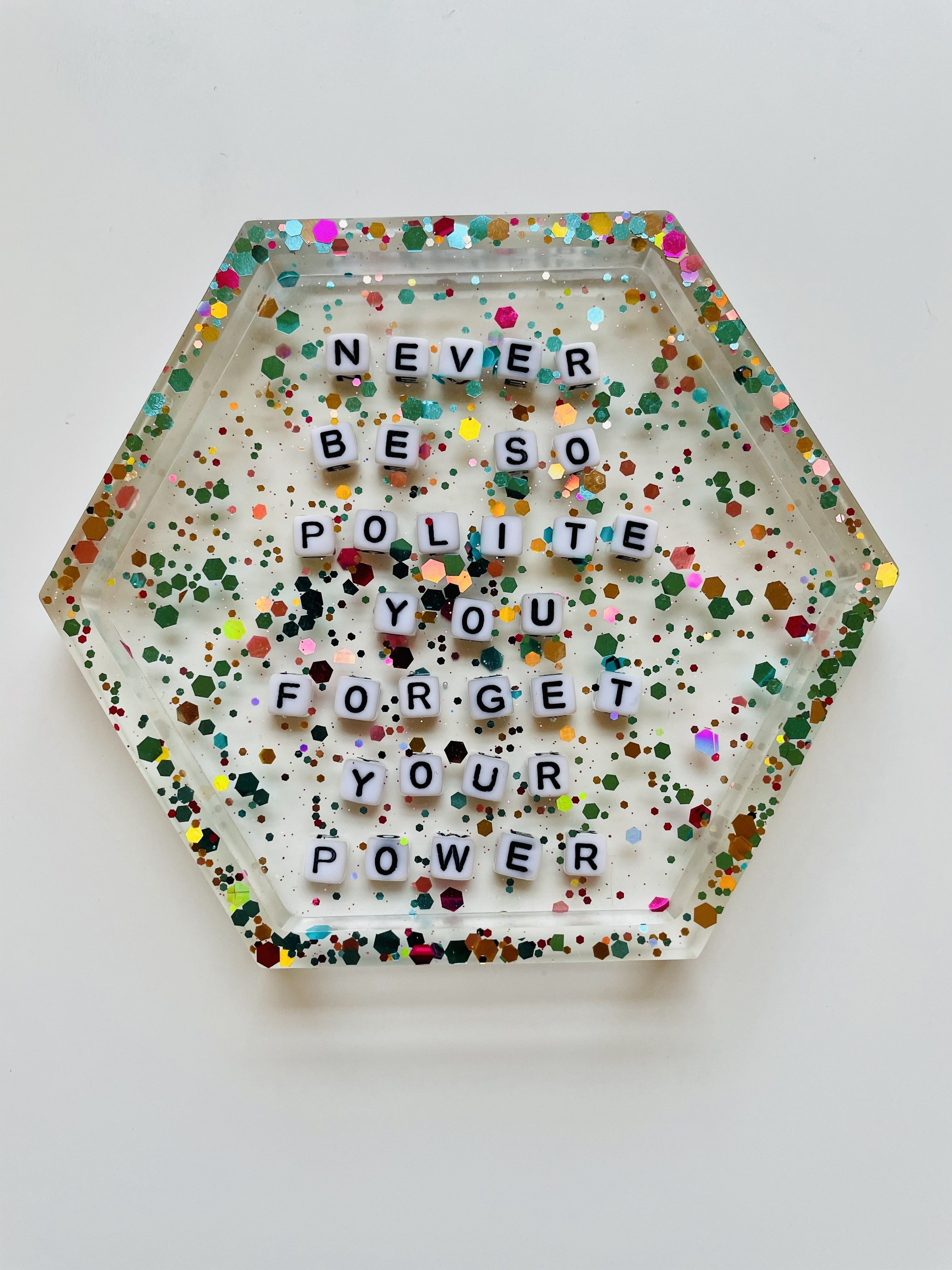"hexagon-shaped coaster with rainbow glitter and letter beads that say ""Never be so polite you forget your power"""