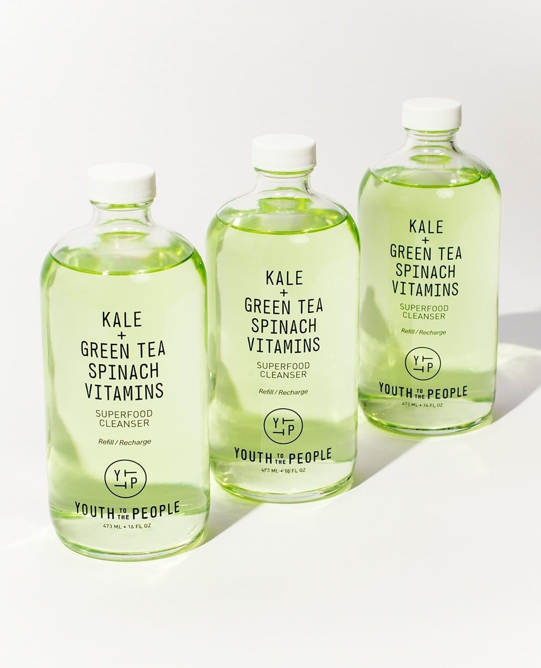 Three large glass bottles of face cleanser