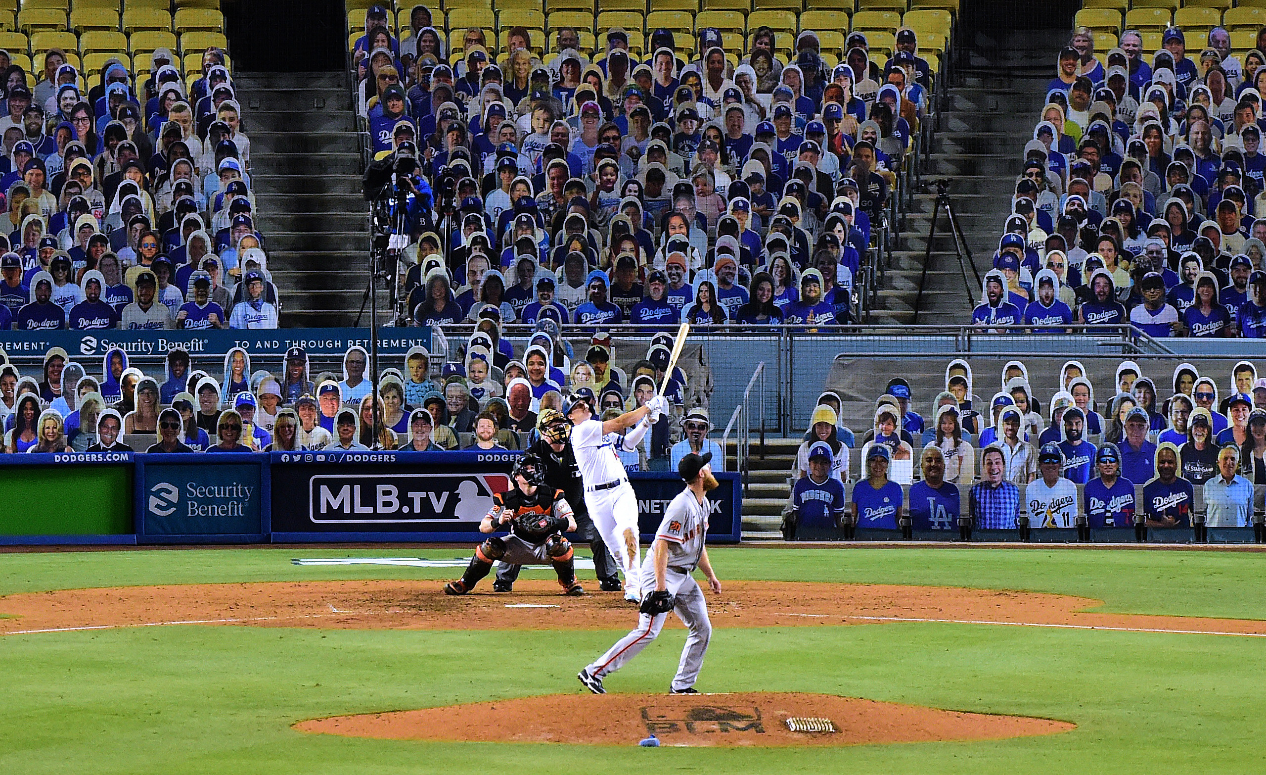 Hernandez hits the baseball while behind him the stadium is filled with cutouts of people in the stands