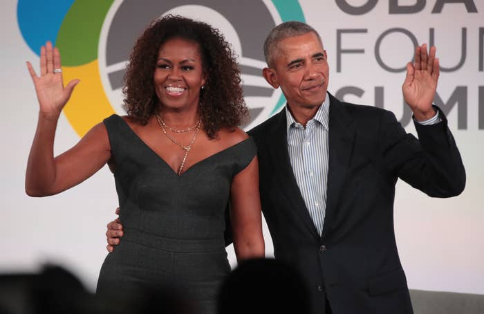 Michelle and Barack Obama stand, with Barack's arm around Michelle's waist, and wave at an audience