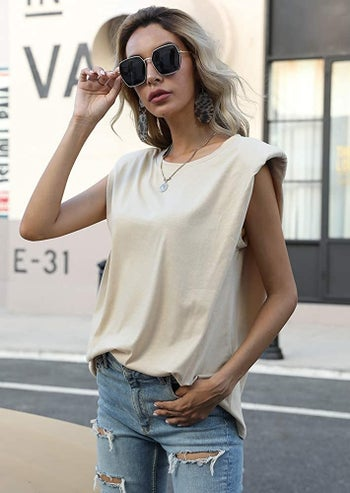 model in white sleeveless shoulder pad top and jeans