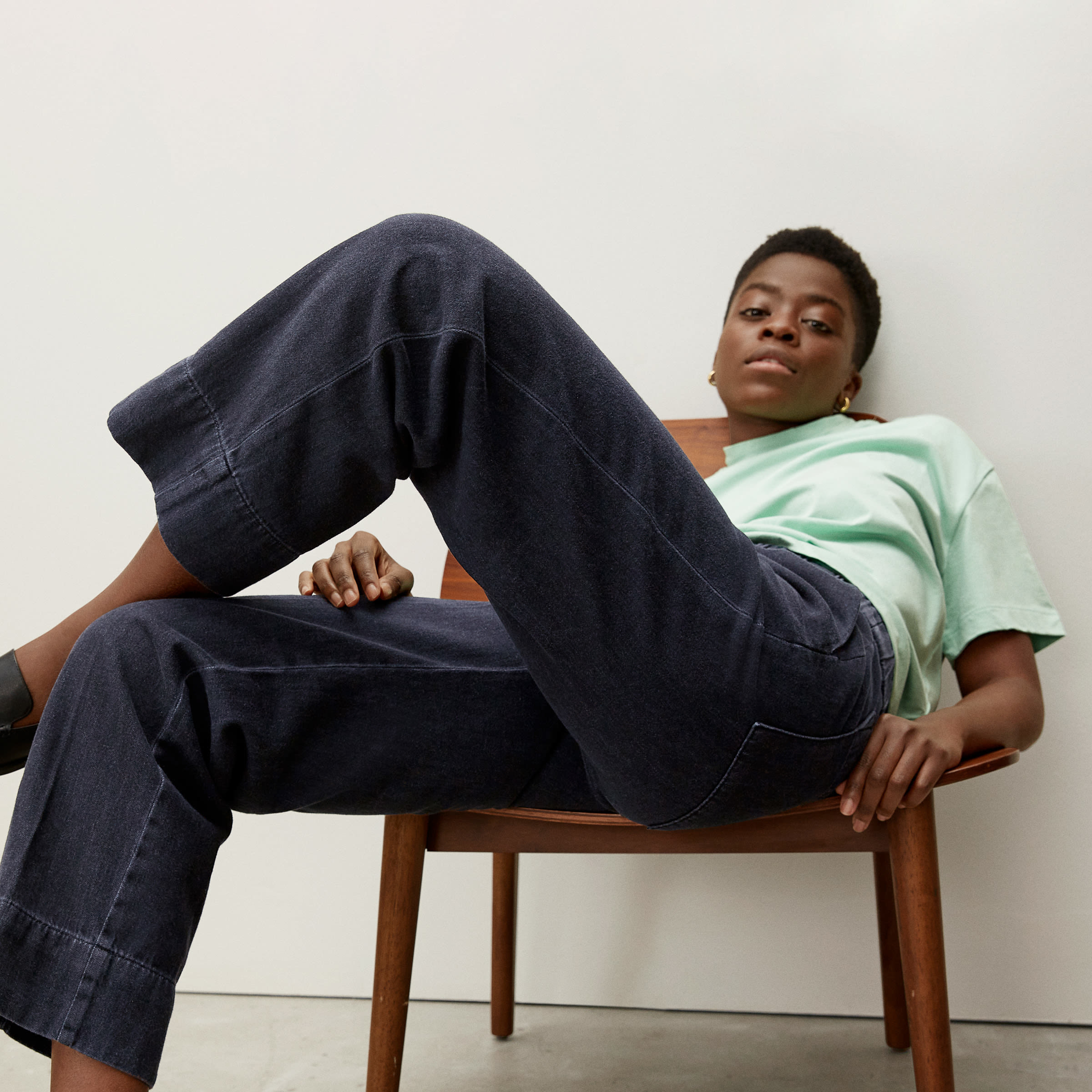 model wears charcoal-colored straight leg jeans with mint T-shirt