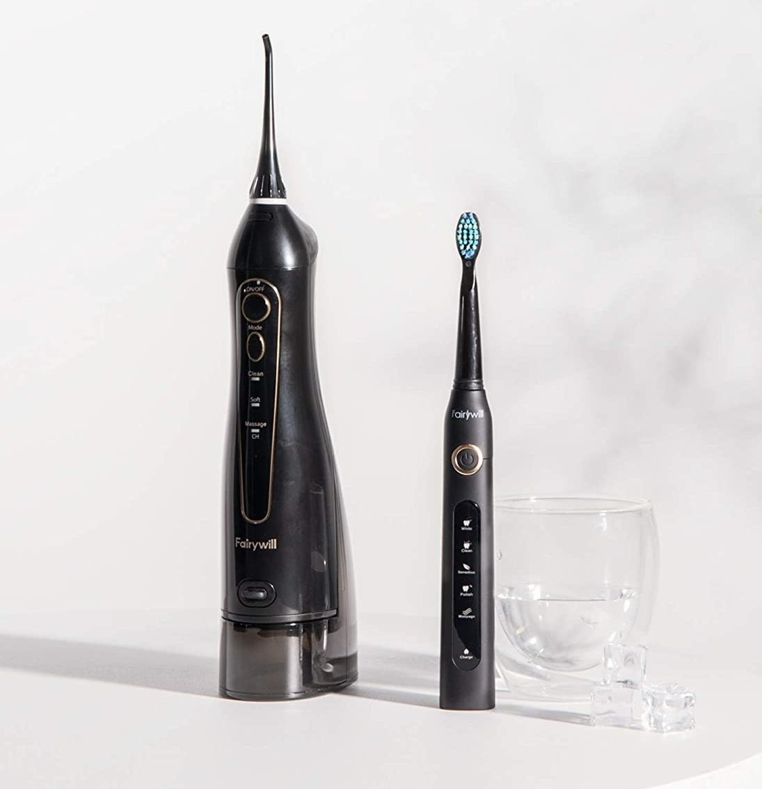 the flosser and toothbrush duo on a table next to a glass