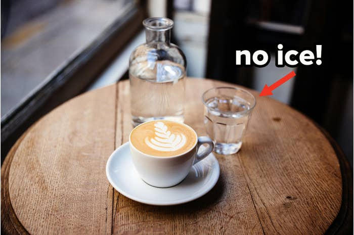 """A table with a full cappuccino, water carafe, and water glass with text """"no ice!"""""""