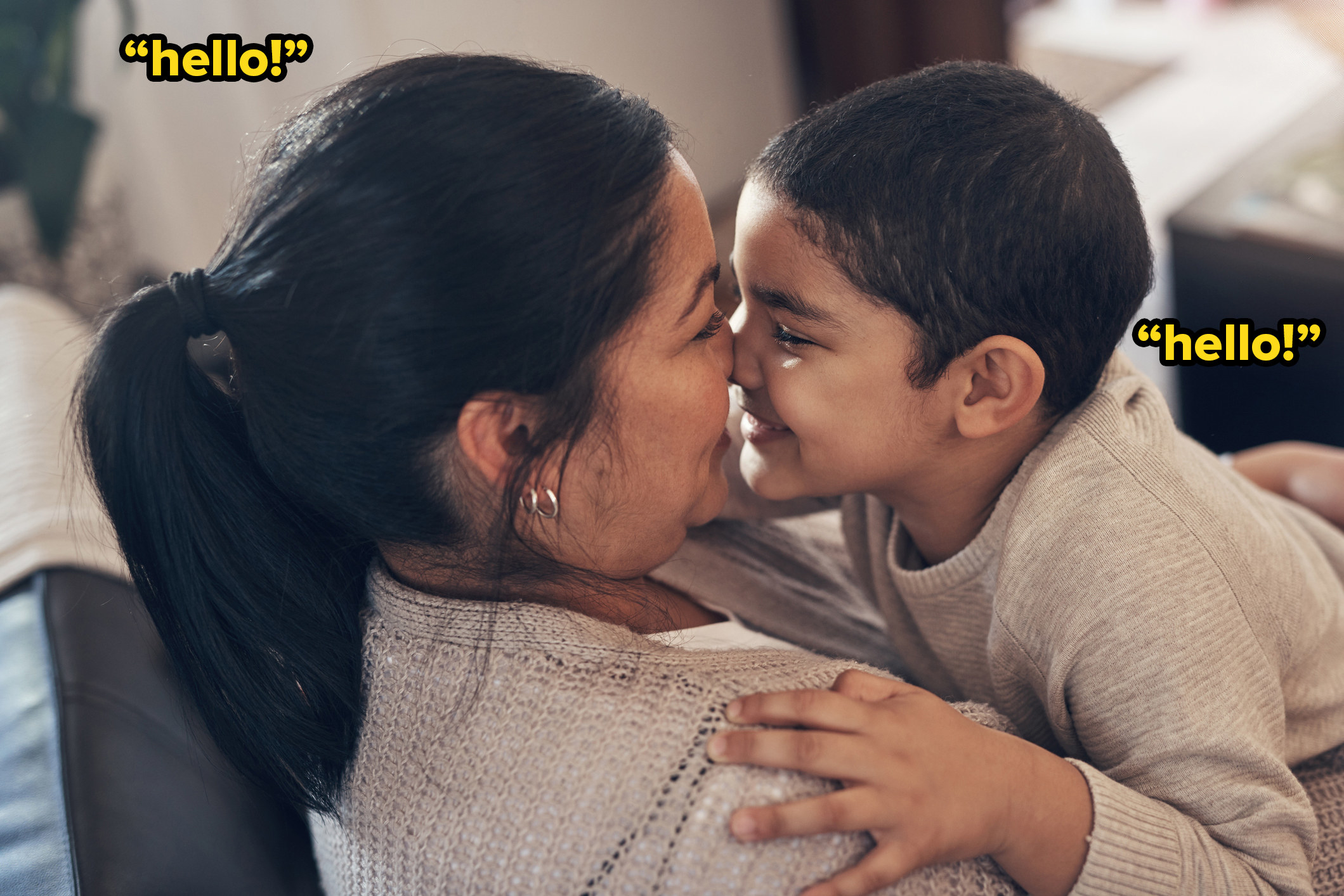 """A woman and her young son laugh and touch noses with added text: """"hello!"""""""