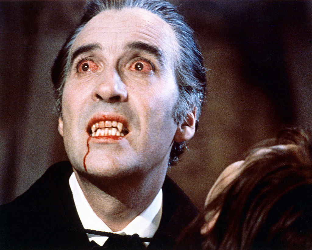 Dracula with bloodshot eyes and blood dripping out of his mouth after sucking the neck of a poor victim