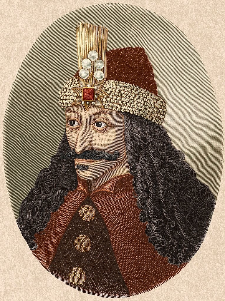 Dracula with long dark hair and a mustache wearing an ornate headpiece