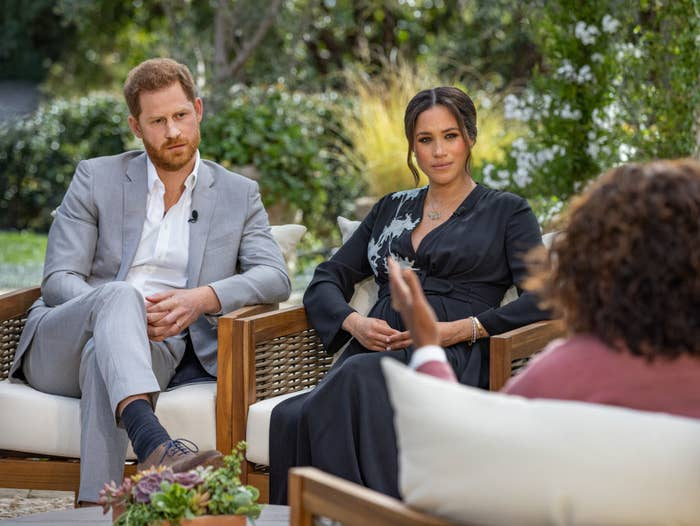 Harry and Meghan listening to Oprah during their outdoor sit-down interview