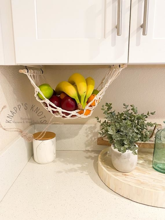 the fruit hammock with bananas and apples in it
