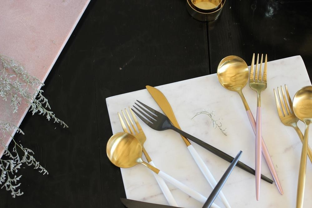 gold-dipper forks, knives, and spoons with black, white, and pink handles