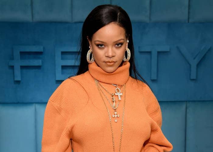 Rihanna wears an orange sweater in front of a Fenty sign