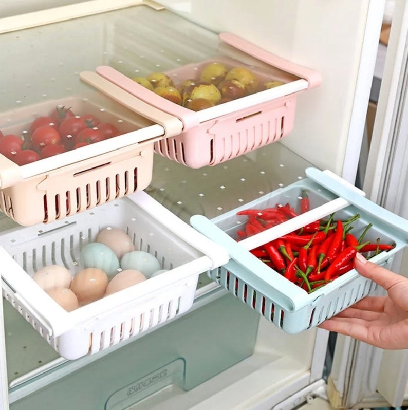 a hand pulling out one of the pastel-colored drawers filled with chili peppers in a fridge