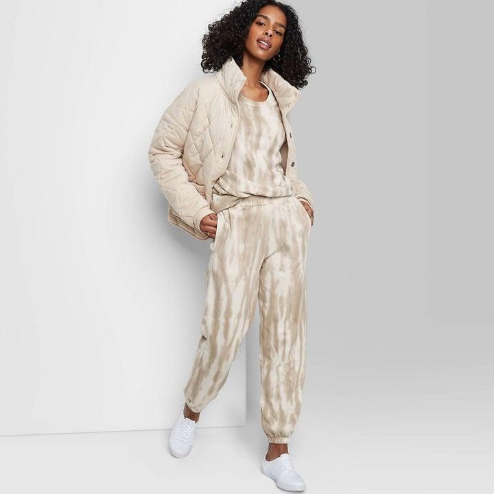 a model wearing the sweatpants in beige tie dye