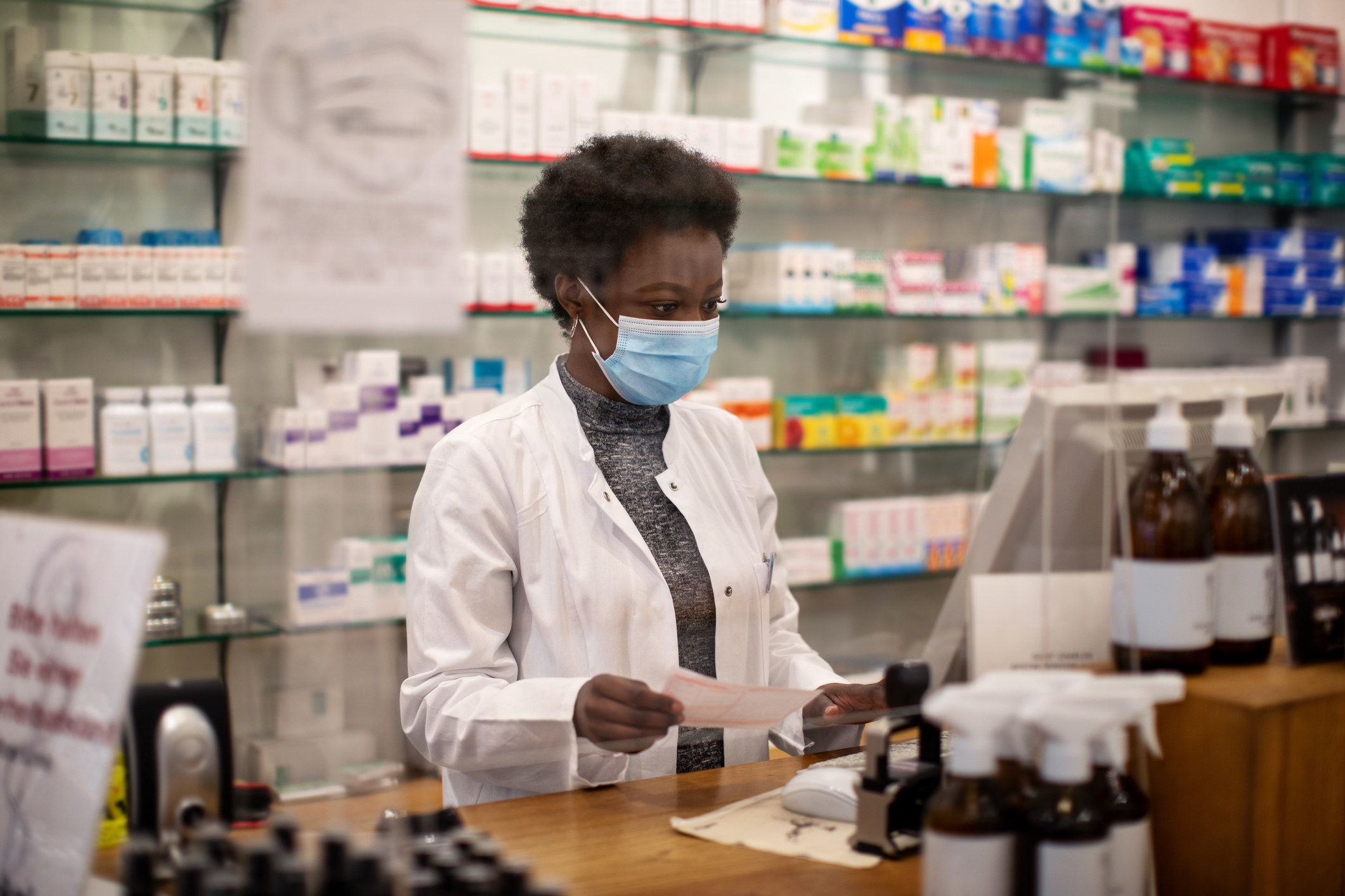 Pharmacist working during COVID - wearing a mask while working behind a plastic protected shield