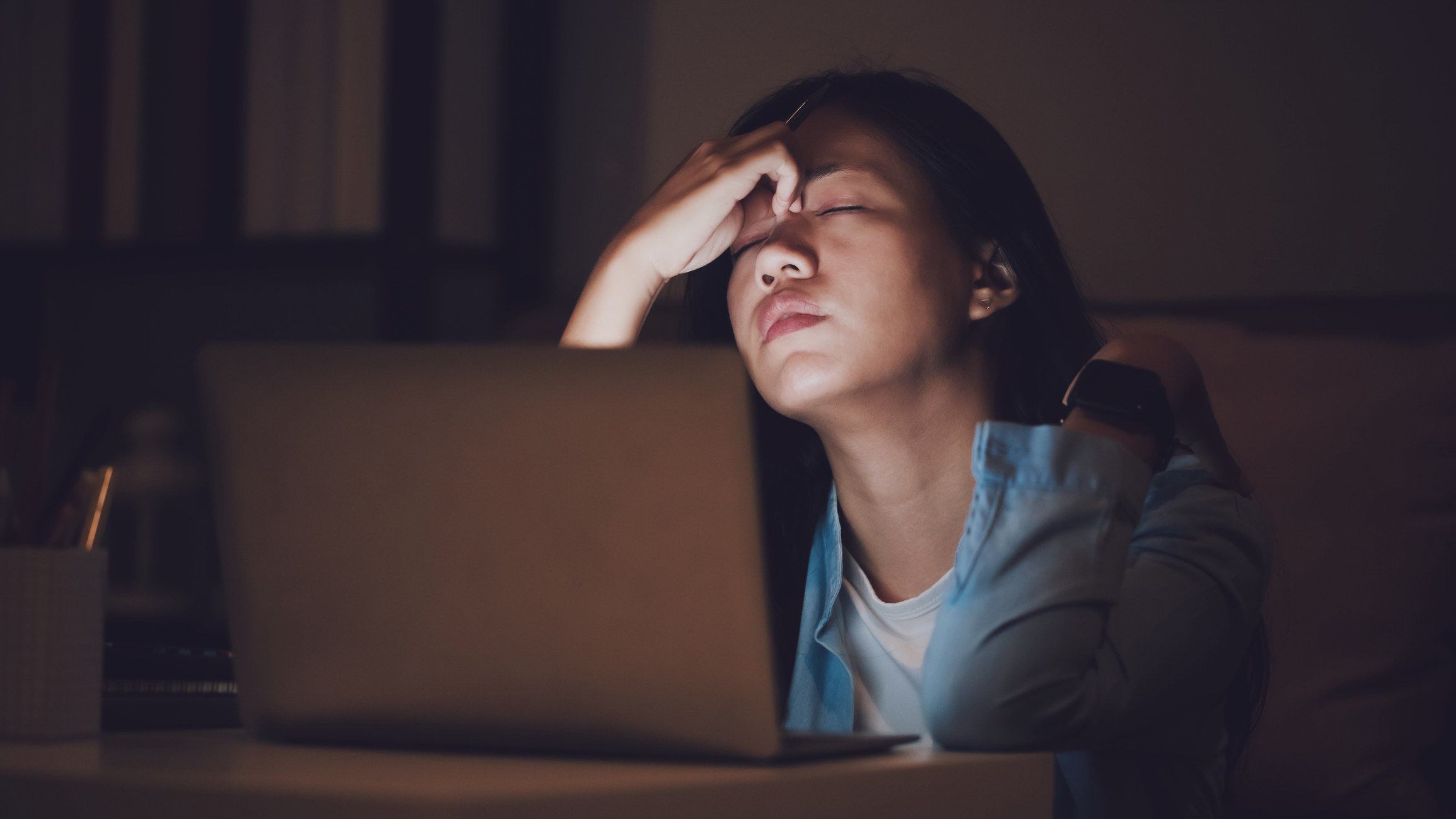 Woman sitting tiredly behind her computer