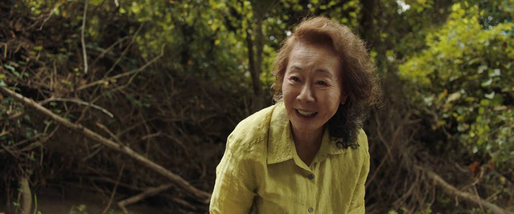 An older woman in a yellow shirt in front of plants outdoors in a still from Minari