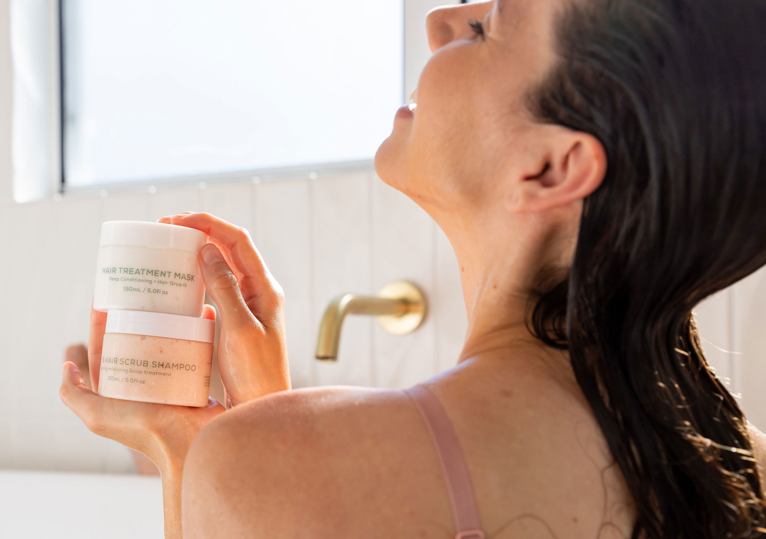A model in a bathtub holding the containers of the scalp scrub and hair treatment mask