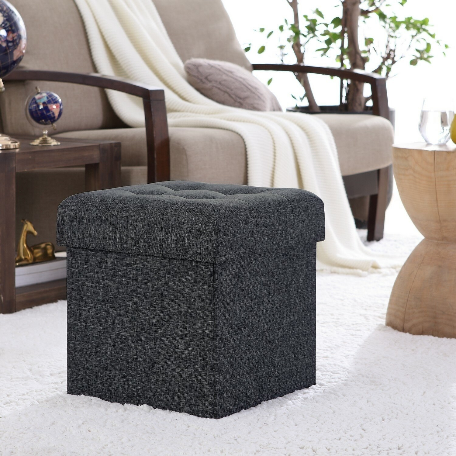 The black Lambertville Foldable Tufted Square Cube Foot Rest Storage Ottoman in a living room