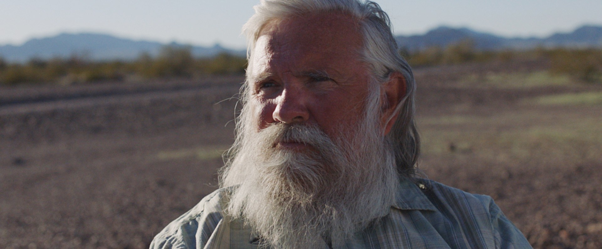 An older man with a beard in front of a desert background