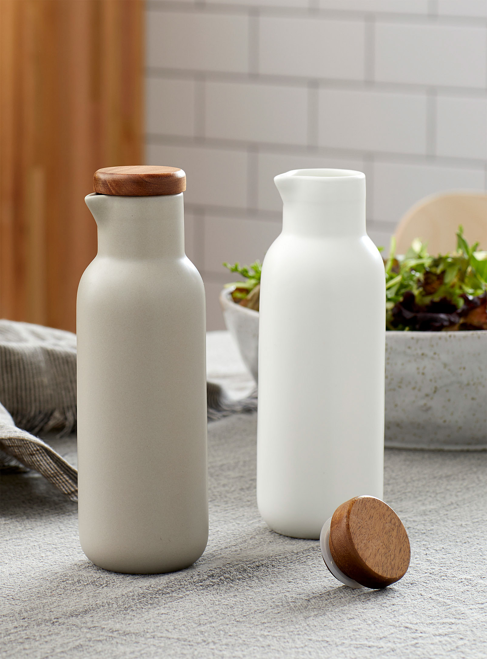 A pair of matte porcelain oil and vinegar cruets on a kitchen counter