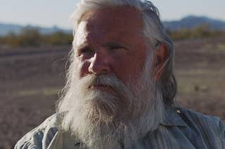An older man with a beard in front of a desert background.