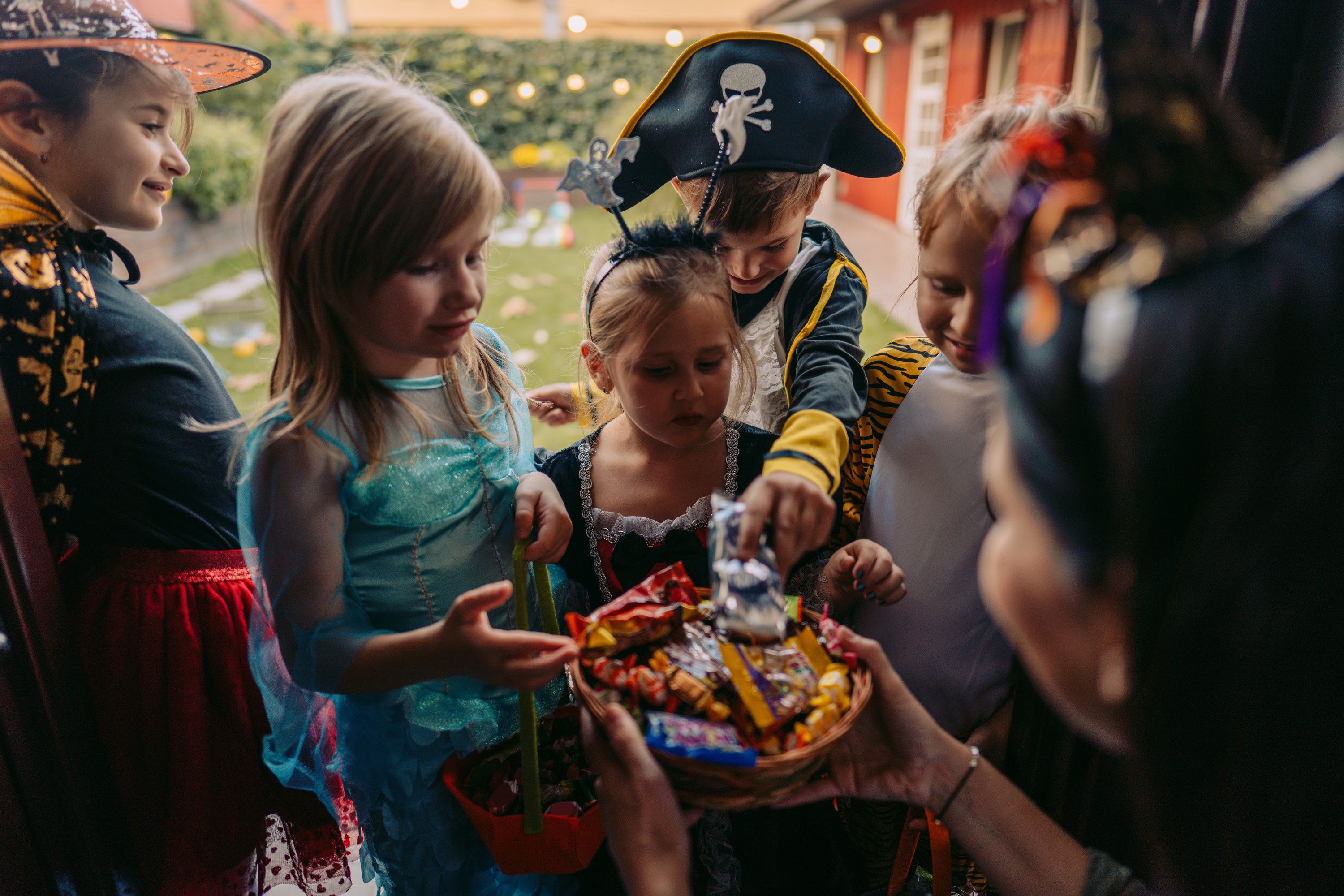 Children dressed up in Halloween costumes grabbing candy from a neighbor holding up a bowl full of treats