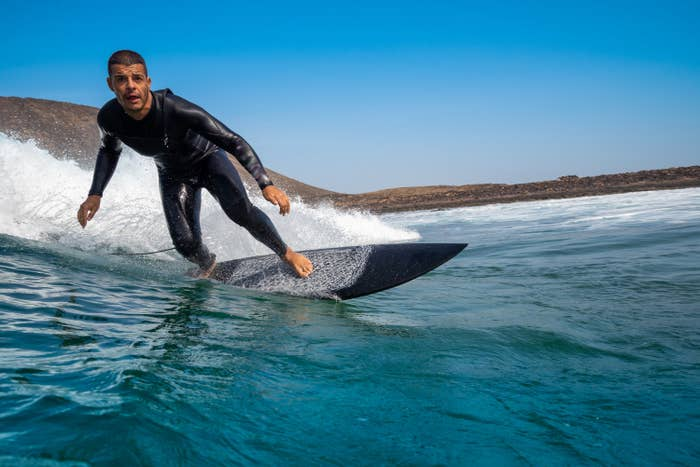Surfer in wet suit riding surfboard in ocean